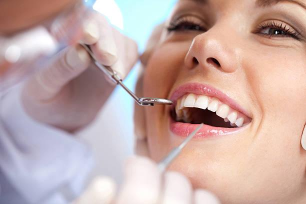 Smiling woman having her teeth worked on